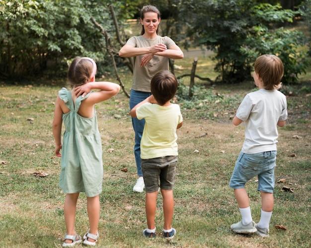 Pełne ujęcie dzieci i nauczyciela grających na świeżym powietrzu