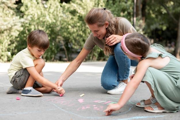 Pełne ujęcie dzieci i nauczyciela rysujących na ziemi
