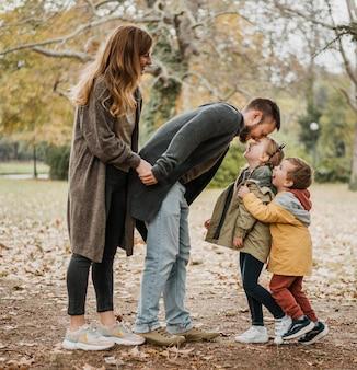 Pełne ujęcie dzieci i rodziców w plenerze