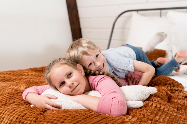 Pełne ujęcie dzieci leżących w łóżku