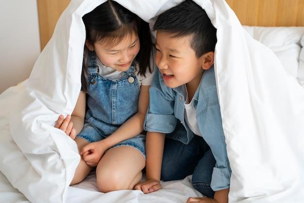 Pełne ujęcie dzieci pod kocem