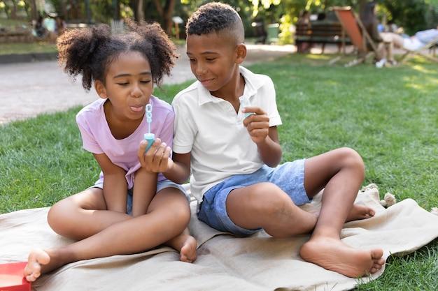 Pełne ujęcie dzieci robiących bańki mydlane