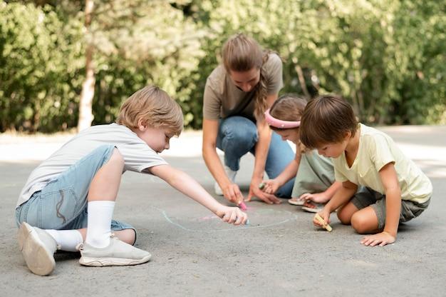 Pełne ujęcie dzieci rysujące na ziemi