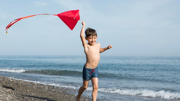 Pełne ujęcie dzieciaka biegającego na plaży