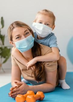 Pełne ujęcie dzieciaka i kobiety w maskach