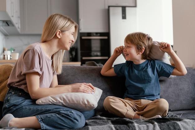 Pełne ujęcie dzieciaka i matki na kanapie