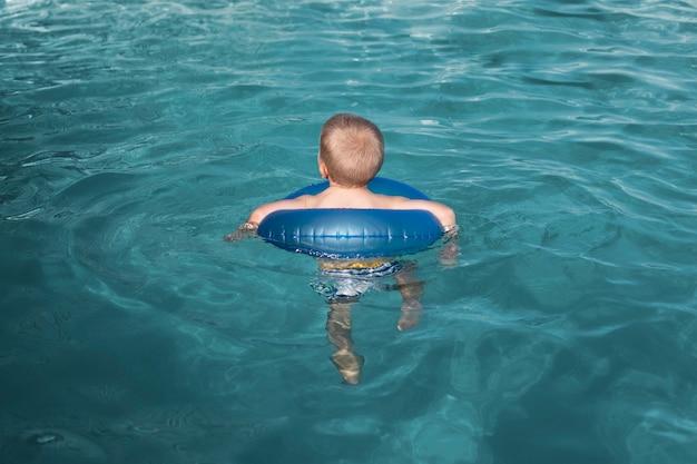 Pełne ujęcie dzieciaka pływającego z kołem ratunkowym