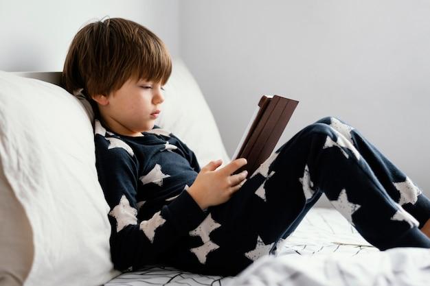 Pełne ujęcie dzieciaka siedzącego w łóżku