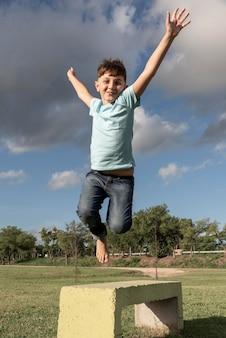 Pełne ujęcie dzieciaka skaczącego na zewnątrz