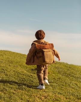 Pełne ujęcie dzieciaka z plecakiem