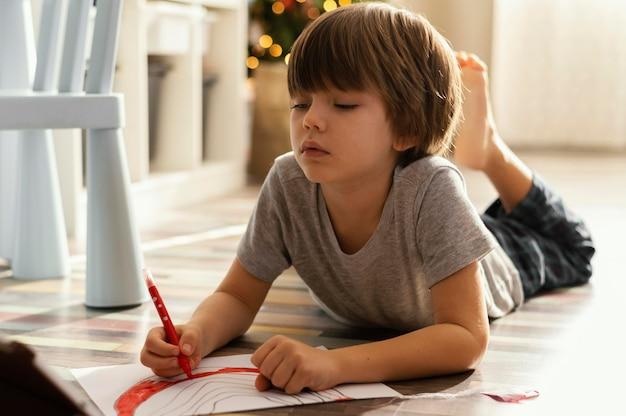 Pełne ujęcie dziecka rysującego na podłodze
