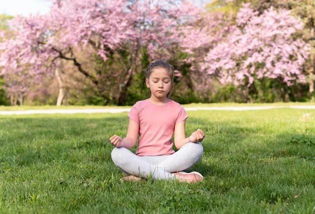 Pełne ujęcie dziecko medytuje na trawie