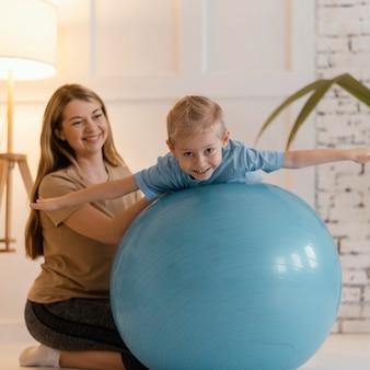 Pełne ujęcie dziecko na siłowni ćwiczenia piłki