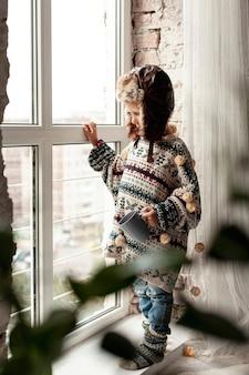 Pełne ujęcie dziecko z kubkiem w pobliżu okna