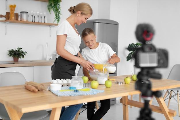 Pełne ujęcie dziewczyny i kobiety gotującej
