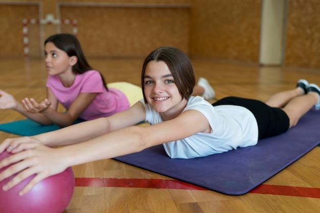 Pełne ujęcie dziewczyny na matach do jogi