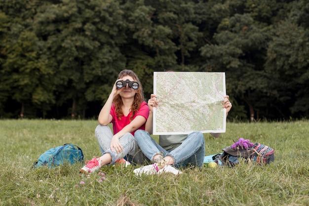 Pełne ujęcie dziewczyny z lornetką i mapą