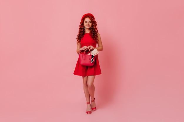 Pełne ujęcie eleganckiej kobiety w szpilkach i czerwonej sukience. kobieta z czerwonymi włosami, trzymając torbę z gazetą w środku.