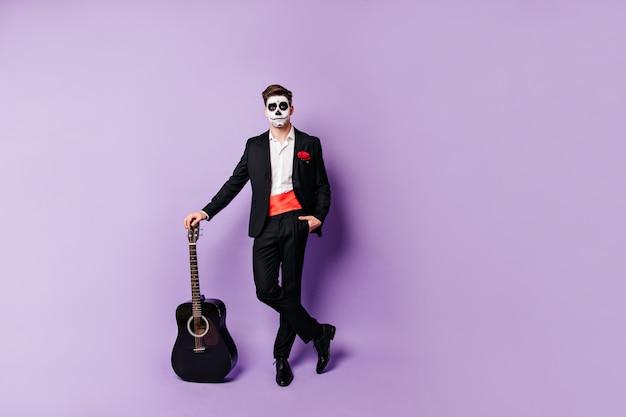 Pełne ujęcie faceta relaksującego się przy gitarze. mężczyzna z pomalowaną twarzą w hiszpańskim garniturze patrzy w kamerę.