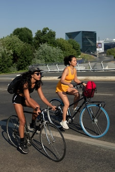 Pełne ujęcie kobiet jeżdżących na rowerach w mieście