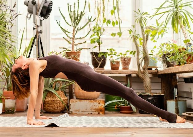 Pełne ujęcie kobiety ćwiczeń wewnątrz
