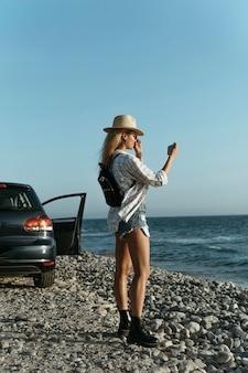 Pełne ujęcie kobiety fotografującej morze samochodem