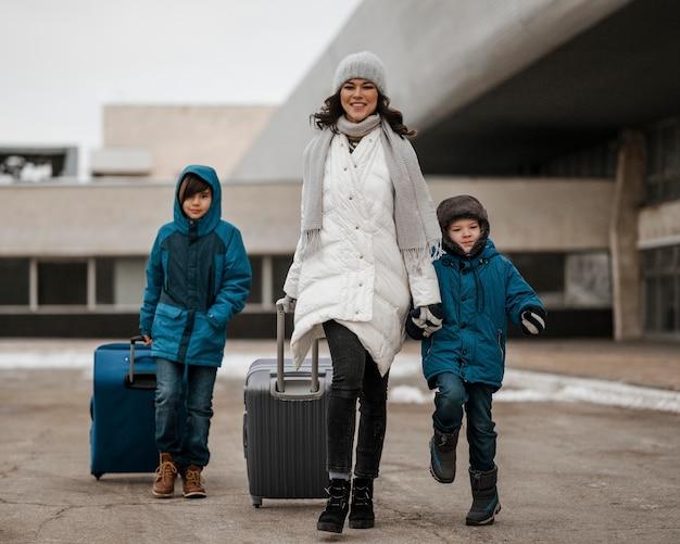 Pełne ujęcie kobiety i dzieci w podróży