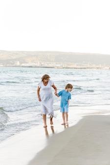 Pełne ujęcie kobiety i dzieciaka na plaży