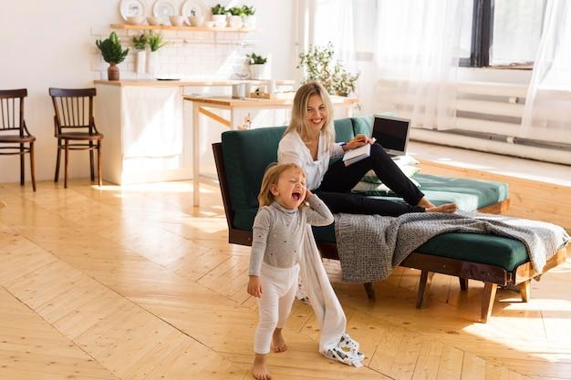 Pełne ujęcie kobiety i dziecka w domu