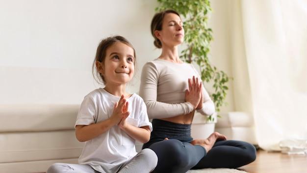 Pełne ujęcie kobiety i dziewczyny podczas medytacji