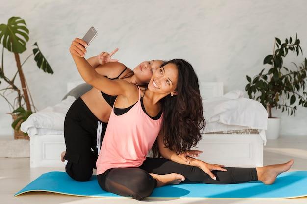 Pełne ujęcie kobiety i dziewczyny przy selfie