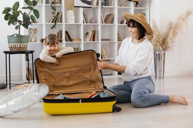 Pełne ujęcie kobiety i dziewczyny z bagażem