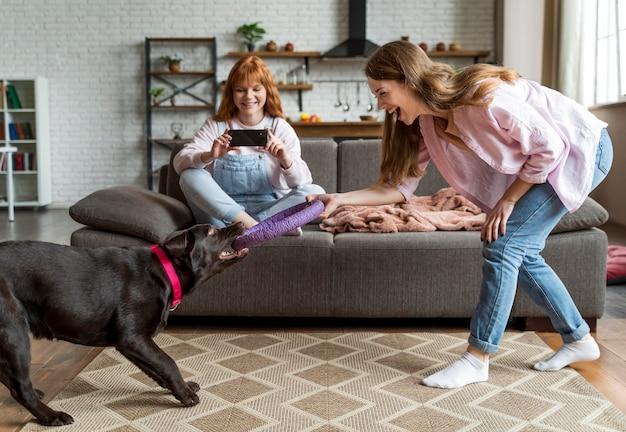 Pełne ujęcie kobiety i psa podczas zabawy