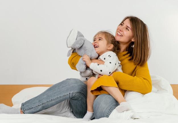 Pełne ujęcie kobiety i uśmiechnięte dziecko