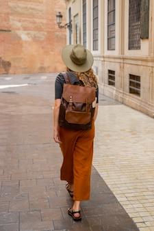 Pełne ujęcie kobiety idącej przez miasto