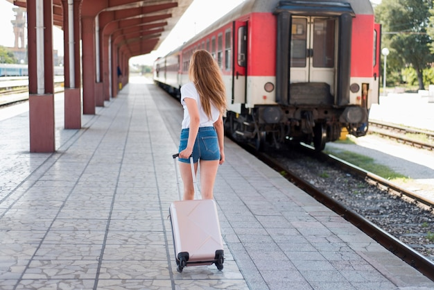 Pełne ujęcie kobiety idącej z bagażem na stacji kolejowej