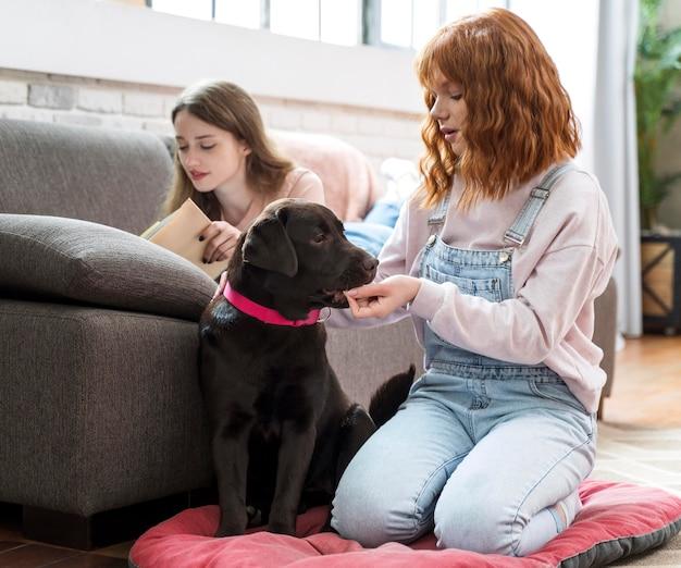Pełne ujęcie kobiety karmienia psa