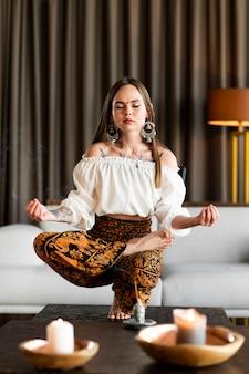 Pełne ujęcie kobiety medytującej w środku