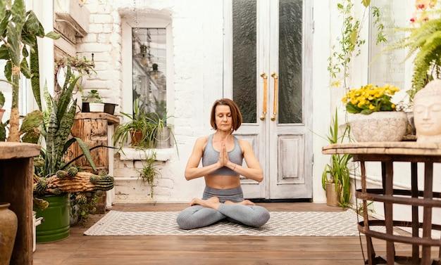 Pełne ujęcie kobiety medytuje w pomieszczeniu