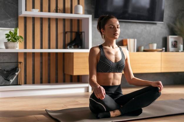 Pełne ujęcie kobiety na macie do jogi