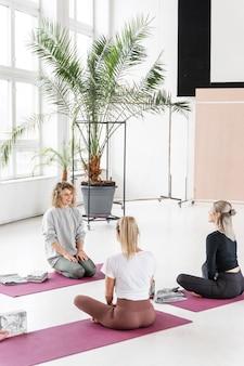 Pełne ujęcie kobiety na matach do jogi