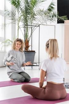 Pełne ujęcie kobiety na matach na zajęciach jogi