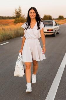 Pełne ujęcie kobiety odchodzącej od samochodu