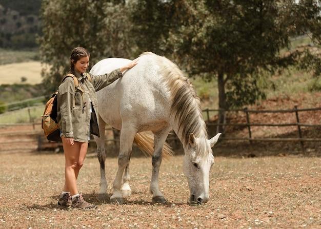 Pełne ujęcie kobiety pieszczoty konia