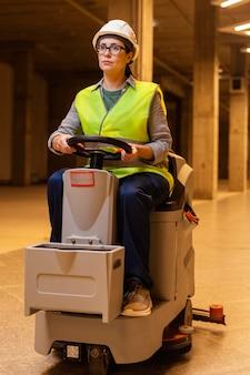 Pełne ujęcie kobiety prowadzącej maszynę do czyszczenia podłóg