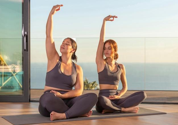 Pełne ujęcie kobiety razem uprawiające jogę