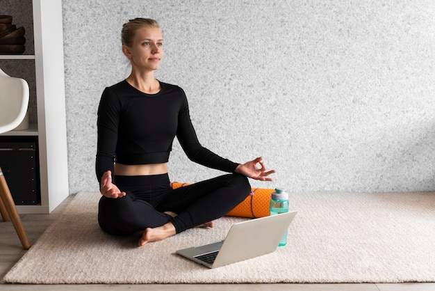 Pełne ujęcie kobiety siedzącej na dywanie