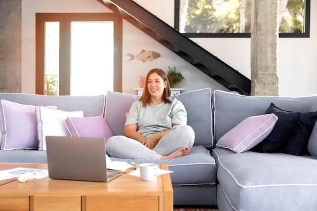 Pełne ujęcie kobiety siedzącej na kanapie