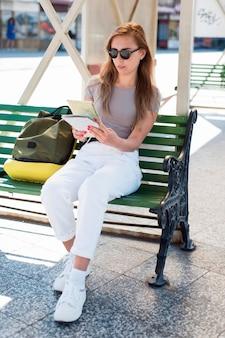 Pełne ujęcie kobiety siedzącej na ławce na stacji