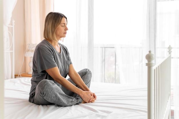 Pełne ujęcie kobiety siedzącej na łóżku